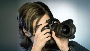 Nainen kuvaa digikameralla
