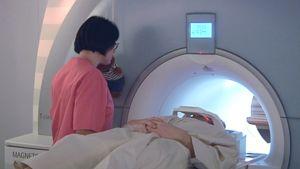Hoitaja antaa ohjeita potilaalle magneettikuvausta varten.