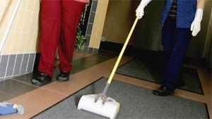 Kaksi siivoojaa siivoaa lattiaa