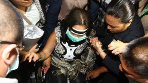 Pyörätuolissa istuvaa Filippiinien entistä presidenttiä Gloria Arroyoa saatetaan ulos Manilan lentoasemalta.