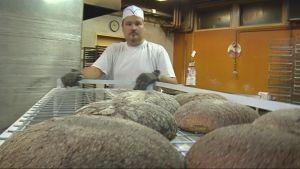 Leipomontyöntekijä ottaa ruisleipiä uunista.