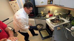 Keittiömestari Jukka Moilanen ottaa kypsennetyt makkarat pois uunista.