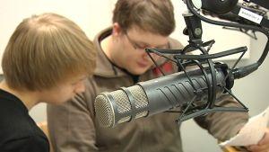 Lähikuvassa mikrofoni, taustalla kaksi oppilasta.