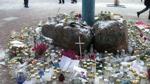 Kynttilöitä, kukkia ja muistosanoja Myyrmannin kauppakeskuksen ulkopuolella räjähdyksen jälkeen.