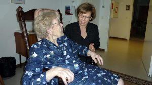 Anni Tiihonen istuu keinutuolissa ja Kristiina Niemelä neuvoo jumppaliikkeitä