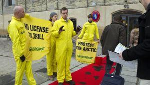Greenpeacen aktivistit osoittavat mieltään öljy-yhtiöiden edustajien saapuessa neuvottelemaan Grönlannin öljynporausoikeuksista.