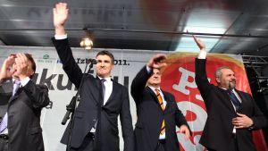 Neljä puoluejohtajaa heiluttaa käsiään yleisölle lavalla.