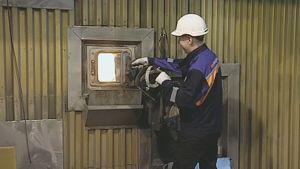 Helsingin energian työntekijä avaamassa Hanasaaren voimalaitoksen polttouunin luukkua.