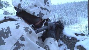 sotilas tähtää lumihangessa