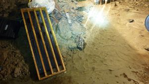 Puulaatikko odottaa kairausnäytteitä, ja kirkas pohjavesi virtaa tunnelin pohjalla.
