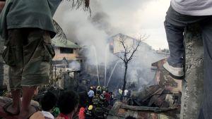 Paranaque-kaupunginosan asukkaat seurasivat lentokoneen maahansyöksyn aihauttaman tulipalon sammutustöitä Manilassa.