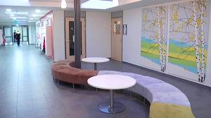 Kuvassa koulun käytävää, oleskelutilaa,seinällä maisemakuva.