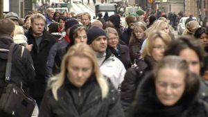Ihmisiä kadulla talvivaatteissa.