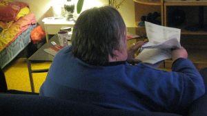 Kuvassa Ritva tarkastelee laskujaan.