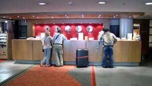 Turisteja hotellin vastaanotossa.