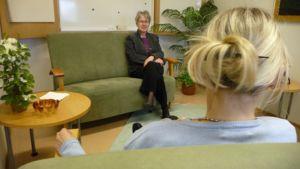 Terapeutti istuu kasvot kameraan päin vihreällä sohvalla. Kuvassa terapiassa käyvä vaaleahiuksinen nainen selin kameraan.