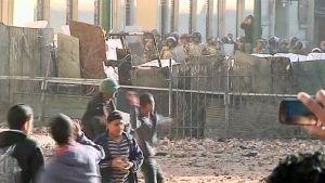 Mellakoitsijat heittelevät poliiseja kivillä Kairon Tahrir-aukiolla.