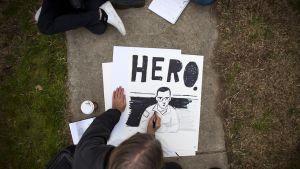"""Nuori mies piirtää tussilla julistetta Bradley Manningista. Kuvan yläpuolella lukee """"HERO"""" (suomeksi sankari)."""