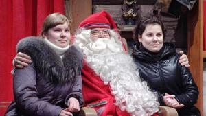 Joulupukki poseeraa kahden naisen kanssa