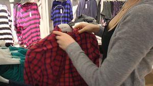 Vaatekaupan myyjä asettaa uusia vaatteita myyntiin.