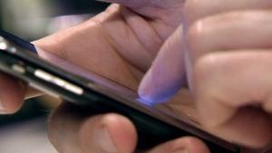 Mies käyttää kosketusnäytöllistä älypuhelinta.
