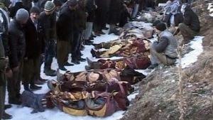 Miehet katselevat surmattujen kyläläisten rivistöä