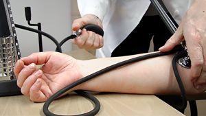 Lääkäri mittaa potilaan verenpainetta.