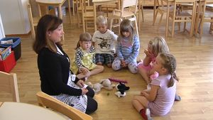 Lapsia istuu ringissä päiväkodin lattialla päiväkodin opettajan edessä.