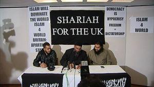 """Islam4UK-järjestön johtaja istuu kahden jäsensä kanssa pitämässä lehdistötilaisuutta. Taustalla paperiarkkeja ja julisteita, joissa lukee muun muassa """"Shariah for the UK"""" ja """"Islam will Dominate the World""""."""