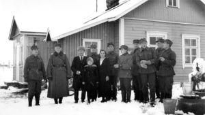 Sotilaita seisoo maalaistalon pihalla isäntäväen kanssa.