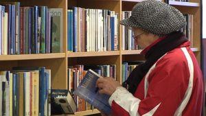 Nainen katselee kirjaa.