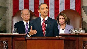 Barack Obama edessä puhujakorokkeella, takana istuvat vanhempi mies puvussaan ja Obamaa hymyillen katsova nainen.