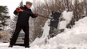 Mies lapioi lunta pois tieltä omakotitaloalueella.