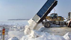 Lunta kaadetaan kuorma-auton lavalta meren jäälle Helsingissä.