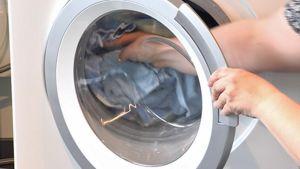 Nainen laittaa pyykkiä pesukoneeseen.