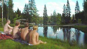 Neljä alastonta ihmistä istuu ruohikolla selkä päin kameraa.