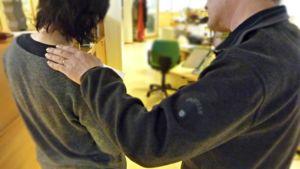 Miehen käsi naisen harteilla