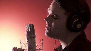 Mikael Konttinen laulaa mikrofoniin studiossa kuulokkeet korvillaan ja silmät kiinni. Taustallaan punertava kajo.