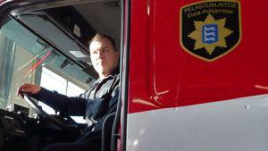 Palomestari Teemu Mäki istuu paloautossa Ylistaron paloasemalla.