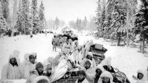 Suomalaisia lumipukuisia sotilaita metsätiellä.