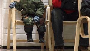 Lapsi istuu käytävällä olevalla tuolilla aikuisen vieressä. Jalat.
