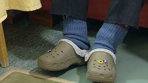 Crocks-jalkineet iäkkään miehen jalassa.
