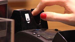 Naisen sormet pistävät maksukortin kortinlukijaan.