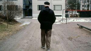 Vanha mies kävelee pihätiellä.