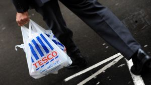 Tummaan pukuun sonnustautunut mies kantaa ruokaostoksia muovipussissa, jossa on Tescon logo.