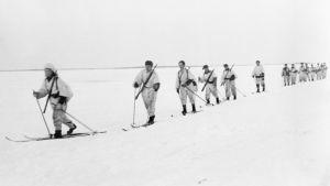 Lumipukuisia sotilaista hiihtää jäällä.