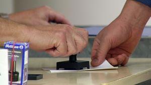 Äänestyslippua leimataan.