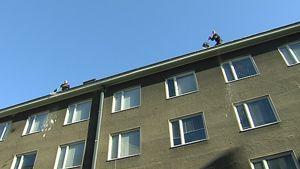 Kaksi miestä pudottaa lunta kivisen kerrostalon katolta.