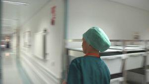 sairaanhoitaja kiiruhtaa käytävällä