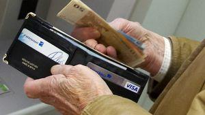 Mies laittaa rahaa lompakkoon